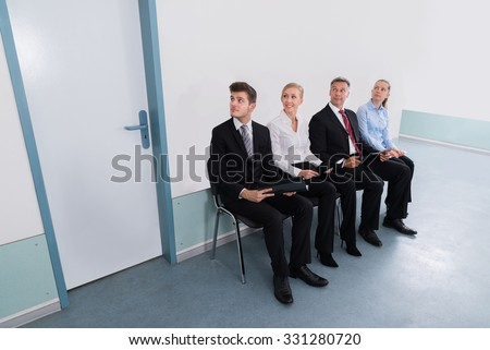 Group Of Applicants Sitting On Chair For Giving Interview In Office