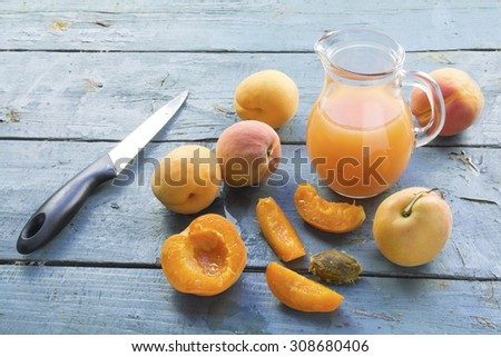 group of apricots, whole and sliced, juice in a glass jug and a knife on an old blue painted wooden table