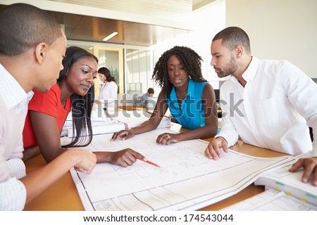 Group Of Architects Discussing Plans In Modern Office #174543044