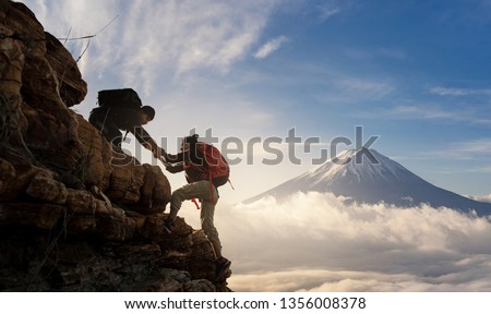 Group of Asia hiking help each other silhouette in mountains with sunlight.