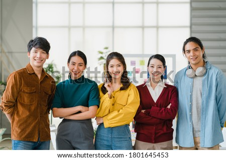Group of Asia young creative people in smart casual wear smiling and arms crossed in creative office workplace. Diverse Asian male and female stand together at startup. Coworker teamwork concept.