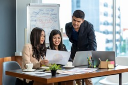 Group Of Asian and Multiethnic Business people with formal suit working and brainstorming together with technology computer in the modern Office, people business group and entrepreneurship concept.