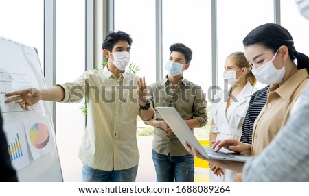 Group of asian business people meeting and working in office and wear mask for protect  prevent infection corona virus covid 19.
