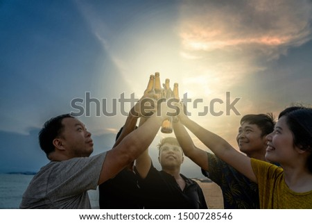 Group of asian cheerful friends have party drinks with cheer beer bottles at the beach when sunset time, celebration and relax when vacation concept #1500728546