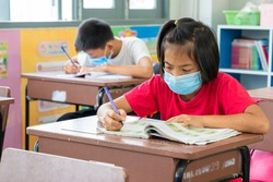 Group of asian children wearing protective mask to Protect Against Covid-19 sitting at desk in classroom,Elementary school,Social Distancing,Coronavirus has turned into a global emergency.