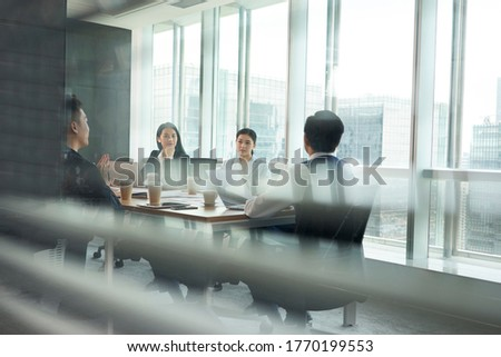 group of asian corporate executives meeting in conference room in office