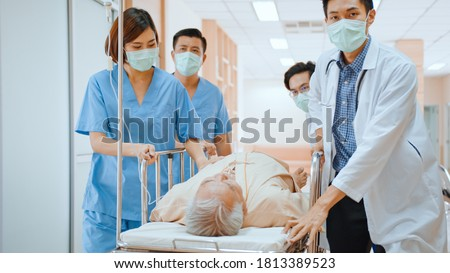 Group of Asian emergency doctor and nurse team wear face mask, push emergency stretcher, transport senior patient in hospital. Health care paramedic service, or medical rescue team operation concept Stock fotó ©