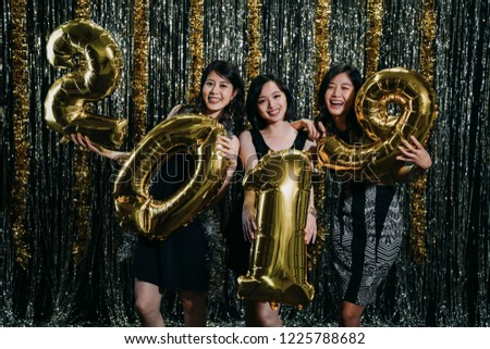 deb1c56e2fad4 Group of asian friends celebrating New Year holding gold 2019 balloons with  silver and golden metallic