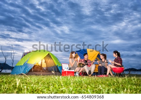 Group of Asian Friends Enjoy Dinner Camping Party and Sing a Song and Play Guitar at the Camp in Summer Evening - Travel and Recreation Concept