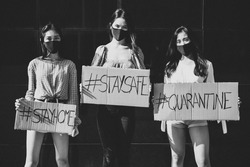Group of asian girls going out after quarantine during coronavirus period. Young women outdoor with safety masks. Showing banners with covid19 most popular hashtags