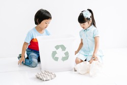Group of Asian kids school sorting garbage and picking up the garbage and putting it in recycling bin in classroom. Recycling and Ecology protection concept.