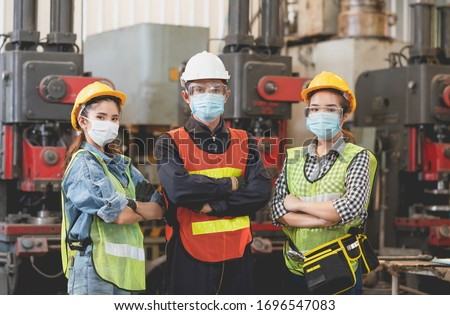 Group of Asian male and female engineers wearing hygienic mask protect with helmet safety in factory Industrial.Coronavirus Protective, safety concept