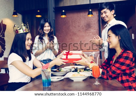 Group of Asian people clapping hands to congratulate each other for birthday gift or rewards during dinner #1144968770