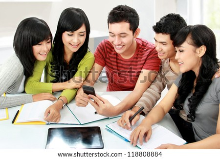 Group of asian students looking at handphone together