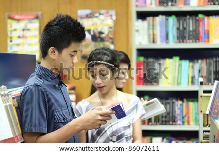 Group of asian students looking for books in the library