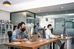 Group of Asian team business people working in office with new normal lifestyle concept. Man and woman wear protective face mask and keep distancing to prevent covid virus after company reopen again.