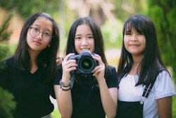 group of asian teenager relaxing in garden with dslr camera in hand
