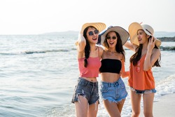 Group of Asian traveler friend girls spending time together at beach in Thailand. Women smiling and laughing feeling fun with happiness enjoy traveling at beach and sea on holiday and vacation.