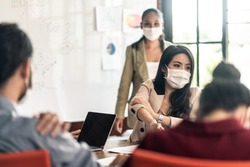 Group of Asian young business people working in office with new normal lifestyle. Man and woman wear protective face mask due covid, brainstorm meeting and share idea in team working as teamwork.