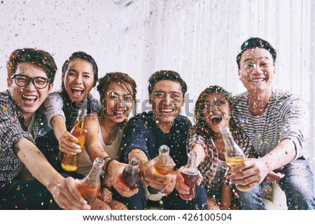Group of Asian young people clinking bottles of beer with you