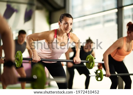 Group of athletes having strength training and lifting barbells in a gym. Focus is o female athlete..  Foto stock ©