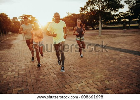 Group of athletes running at the city park. Runners in sportswear training together outdoors. #608661698