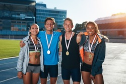 Group of athletes with medals .Two young woman and man together looking at camera and smiling while standing on athletics race track in stadium.