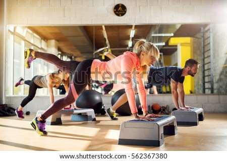 Group of athletes working push ups with one leg up in the air at the gym.
