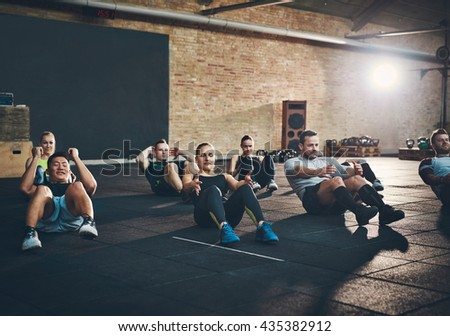 Group of athletic adult men and women performing sit up exercises to strengthen their core abdominal muscles at fitness training