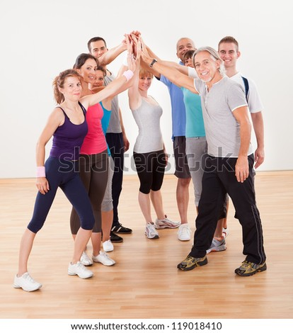 Group of athletic healthy adults in gym giving group high five - stock photo