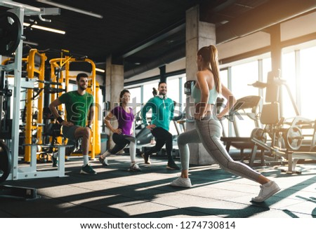 Group of athletic people exercising in a health club