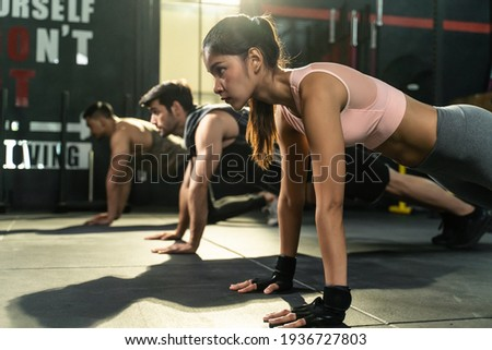 Group of athletic people men and woman with ponytail and gloves workout together. Doing plank for strenght and strong abs musclesin gym for healthy and sporty lifestyle. Sports activity training class