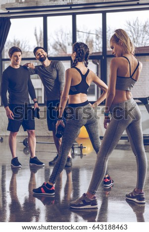group of athletic young people in sportswear exercising at the gym, aerobic fitness concept