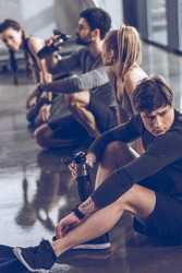 group of athletic young people in sportswear sitting on floor and resting at the gym, group fitness concept