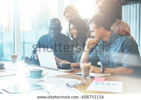 Group of attractive entrepreneurs in meeting with bright windows and cluttered conference table