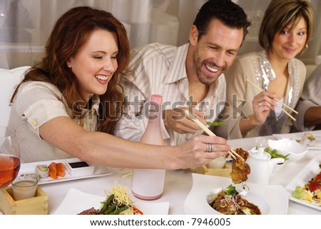 Group of attractive people eating and socializing at a restaurant