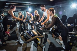 Group of attractive women and men pedaling on a stationary bikes at the gym.