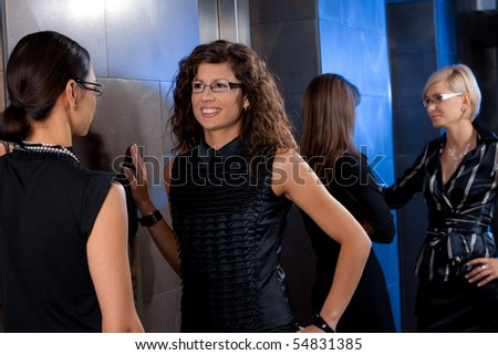 Group of attractive young businesswomen, waiting for lift in office lobby, talking.