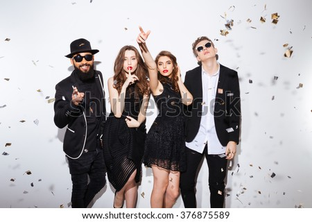 Group of attractive young friends standing ans gesturing over white background