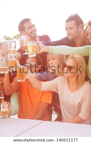 Group of Attractive young People toasting with a delicious Pale Ale  Beer