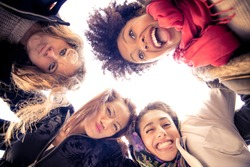 Group of attractive young women of different ethnics hugging in a circle - Four students smiling at camera - Best friends spending time together