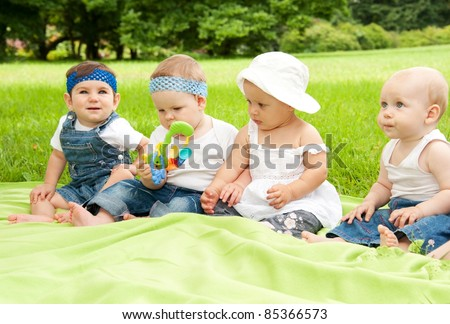 Group of babies outdoors. - stock photo