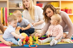 Group of babies toddlers playing with colorful educational toys and mothers in nursery room