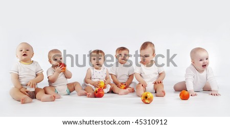 Group of babies with apples sitting on white studio background