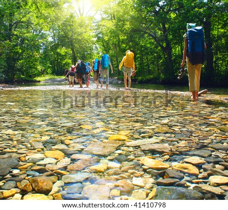 Group of backpackers fording cold river