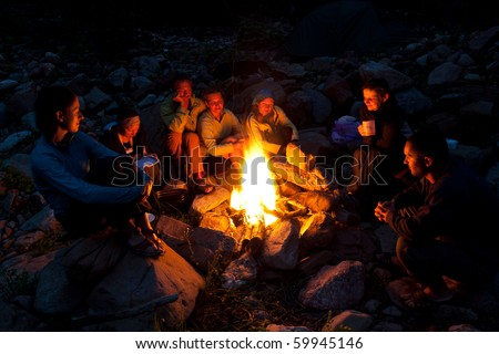 Group of backpackers relaxing near campfire after a hard day, tourist background.
