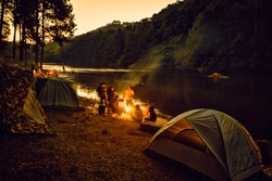 Group of backpackers relaxing near campfire, tourist background.