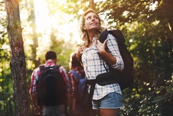 Group of backpacking hikers friends going for forest trekking