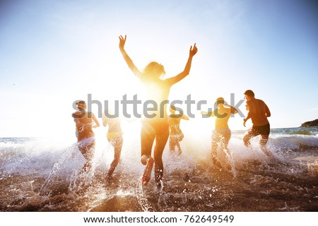 Group of beautiful people having fun, run and jumps at sunset beach