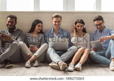 Group of beautiful young people in casual clothes using gadgets and smiling while sitting together on the floor #588275063